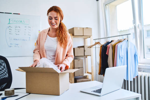 Young online store owner packing delivery into cardboard box in office stock photo