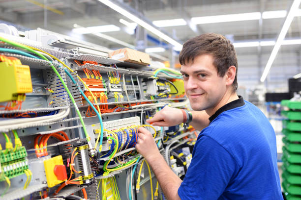 young operator assembles machine in a modern high tech factory - production of switch cabinets for industrial plant stock photo
