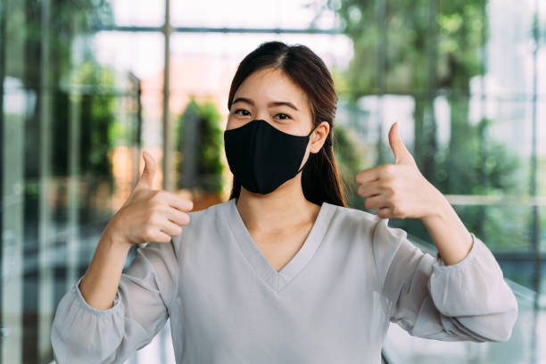 Young optimistic Asian female student giving thumbs up gesture. She's wearing a protective mask (PPE) to avoid air pollution or Corona Virus pandemic for safety stock photo