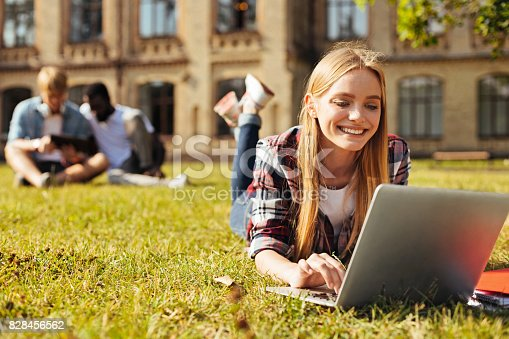 istock Young optimistic woman checking her updates 828456562