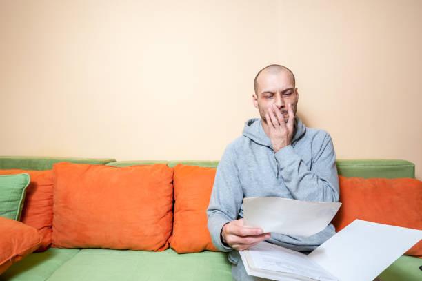 jungen oder mittleren alter kranken mann in der freizeitkleidung befunde auf die papiere von seinem arzt lesen und erkennen, daß er diagnostiziert ein krebs oder andere krankheiten - aids stock-fotos und bilder