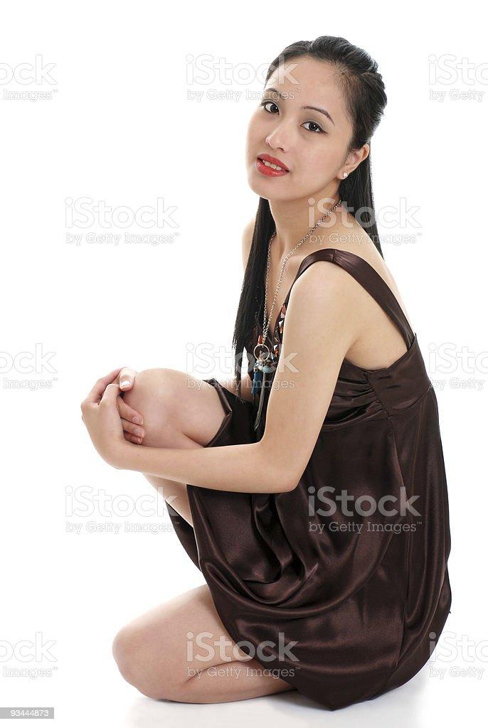 Junge asiatische Frau in einem braunen Kleid sitzt auf Lizenzfreies stock-foto