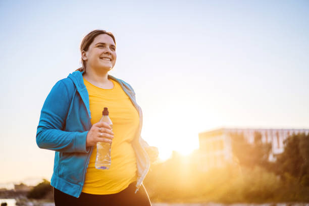 Young overweight woman running stock photo