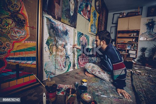 865169666 istock photo Young painter working on a painting in studio 898826240