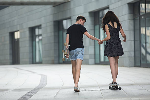 Young pair in love of stylish teenagers ride longboards stock photo
