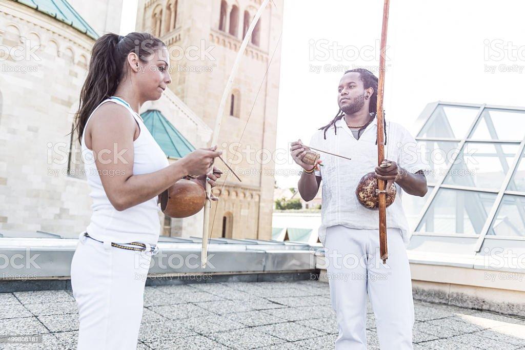 Jovem par parceiros de capoeira, com berimbau instrumento musical em suas mãos - foto de acervo