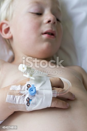 istock Young pale boy in bed with canulla on his hand 454074815