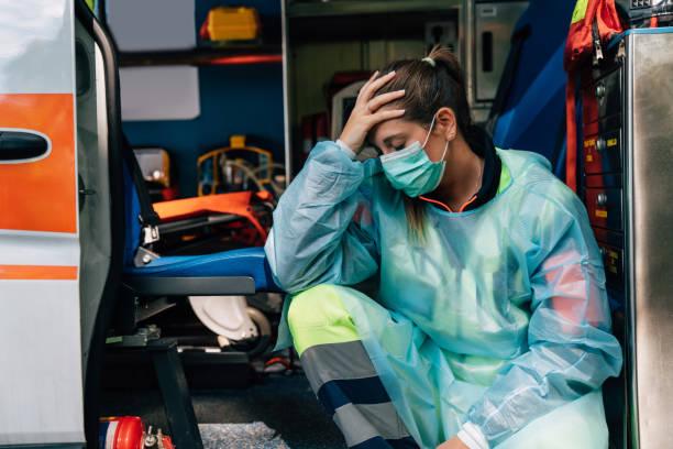 Young paramedic woman is sad, sitting on an ambulance stock photo