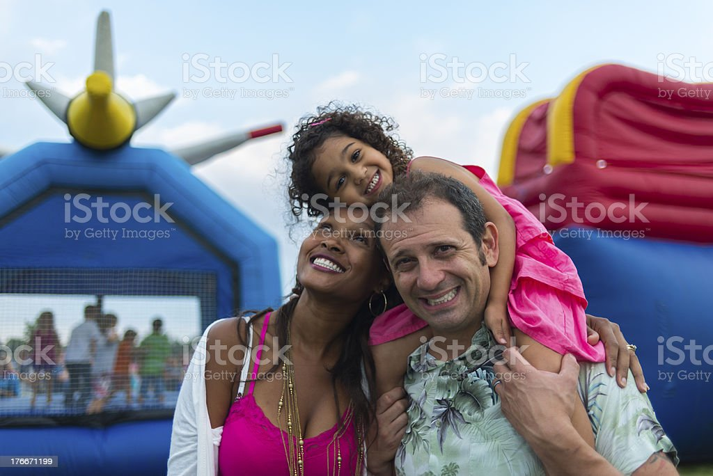Young parents and child at a festival with inflatables stock photo
