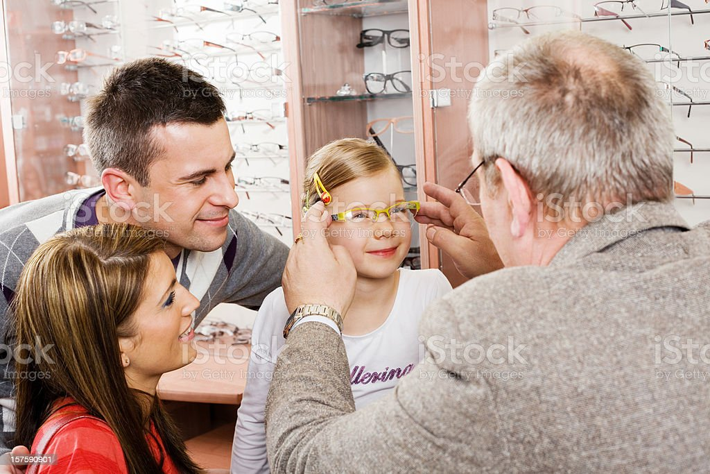 Young Parents And Daughter Shopping For New Glasses Little girl trying on a new pair of glasses at the opticians with her parents standing behind her. 25-29 Years Stock Photo