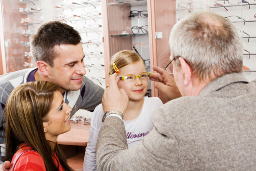 Young Parents And Daughter Shopping For New Glasses Stock Photo - Download Image Now