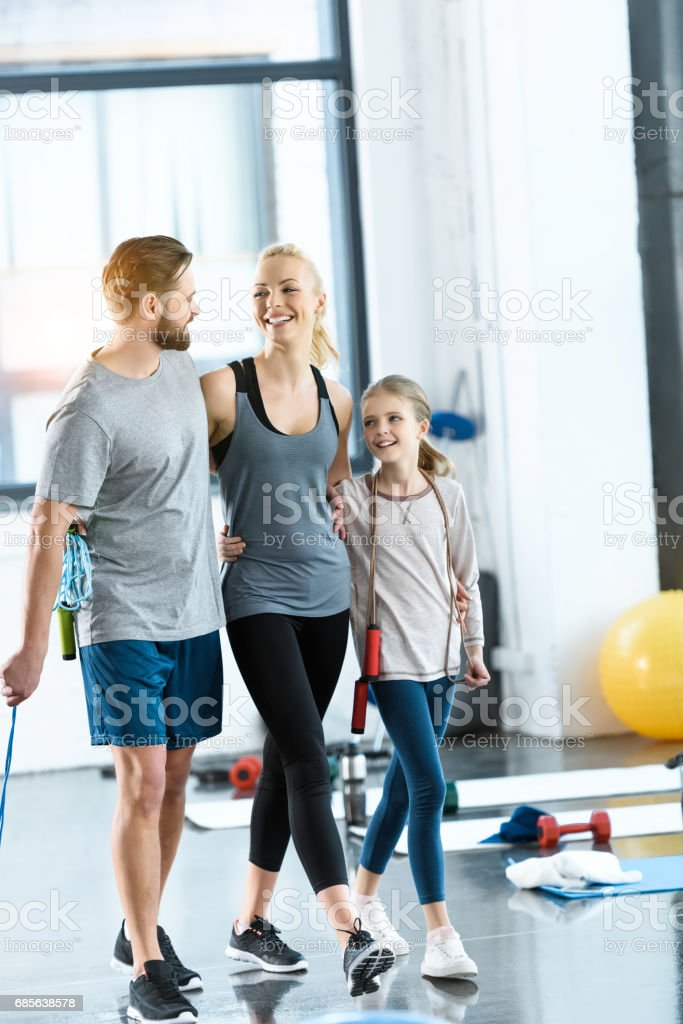 Young parents and daughter with skipping ropes at health club foto de stock royalty-free