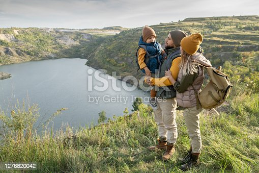 Young parents and their little son with backpacks standing on green grass against lake or river surrounded by mountains while enjoying trip