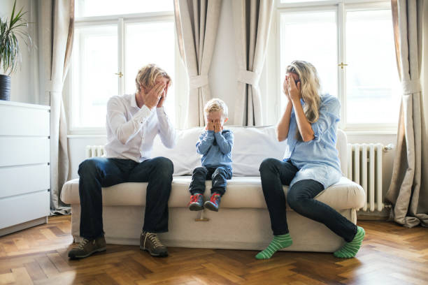 young parents and toddler son sitting on a sofa inside in a bedroom, covering eyes. - mom spying stock photos and pictures