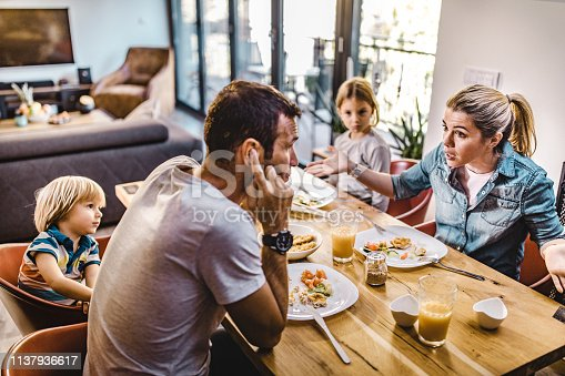 Young couple arguing during lunch time with their children in dining room. Focus is on woman.