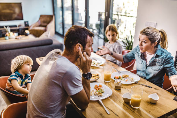 Young parents arguing while having lunch with their kids at home. Young couple arguing during lunch time with their children in dining room. Focus is on woman. relationship difficulties stock pictures, royalty-free photos & images