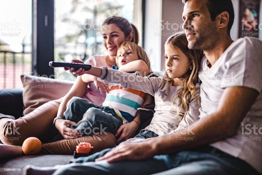 Young parents enjoying with their small kids on sofa while watching TV together. stock photo