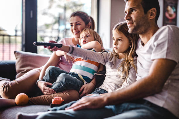 Young parents enjoying with their small kids on sofa while watching TV together. Young happy family watching TV on sofa at home. Focus is on girl changing channels. changing channels stock pictures, royalty-free photos & images