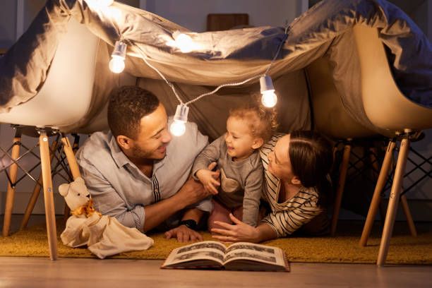 Young parents having fun with their little daughter in handmade tent at home in evening, horizontal shot stock photo