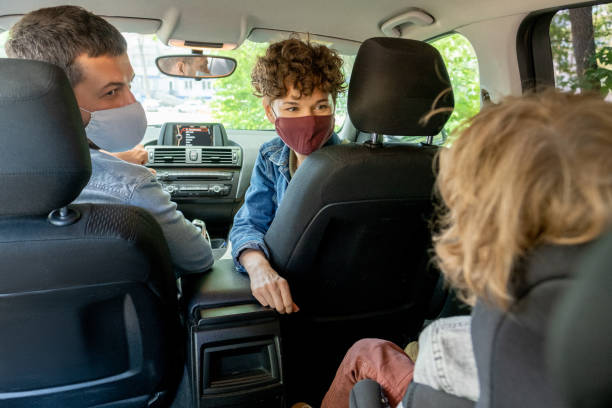 Young parents in protective masks looking at their cute little son on backseat stock photo