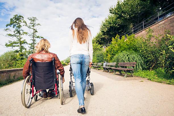 young parents in wheelchair with baby stroller in the park - sommerferien baden württemberg stock-fotos und bilder