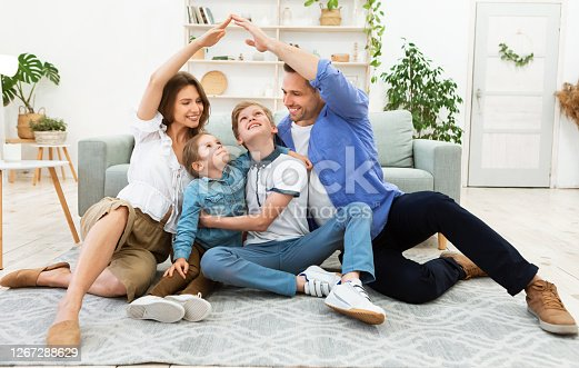 istock Young parents joining hands making roof sitting with children indoor 1267288629