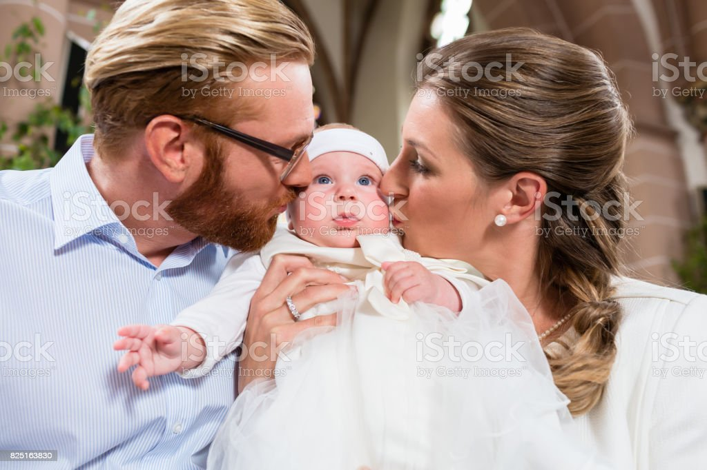 Young parents kiss their baby at the same time after the christening ceremony stock photo