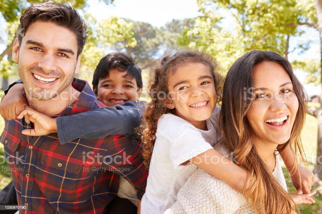 Padres jóvenes piggybacking sus dos hijos al aire libre foto de stock libre de derechos