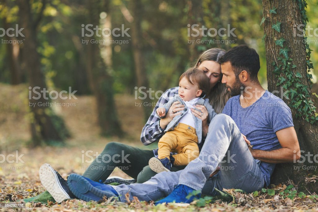 Young parents relaxing outdoors in nature with their baby boy royalty-free stock photo