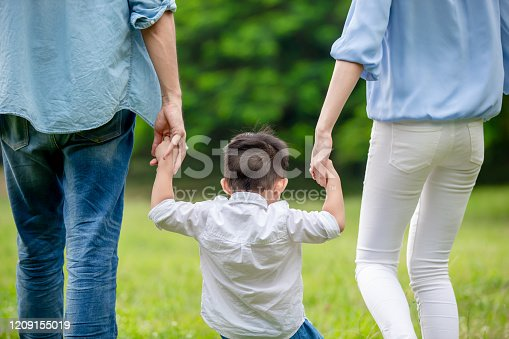young parents and kid holding hand and take a walk in the park