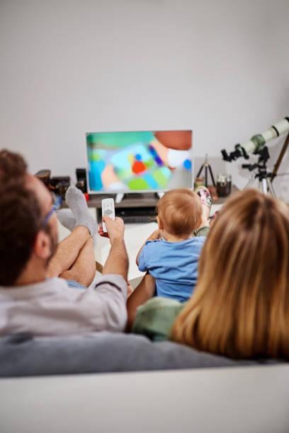 Junge Eltern fernsehen mit baby boy. – Foto