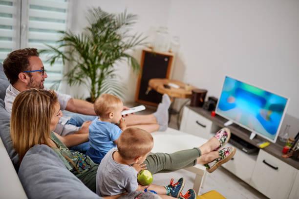 young parents watching tv with baby boys. - tv e familia e ecrã imagens e fotografias de stock