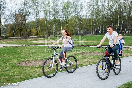 istock Young parents with a little daughter riding a bike in a city park 1013115698
