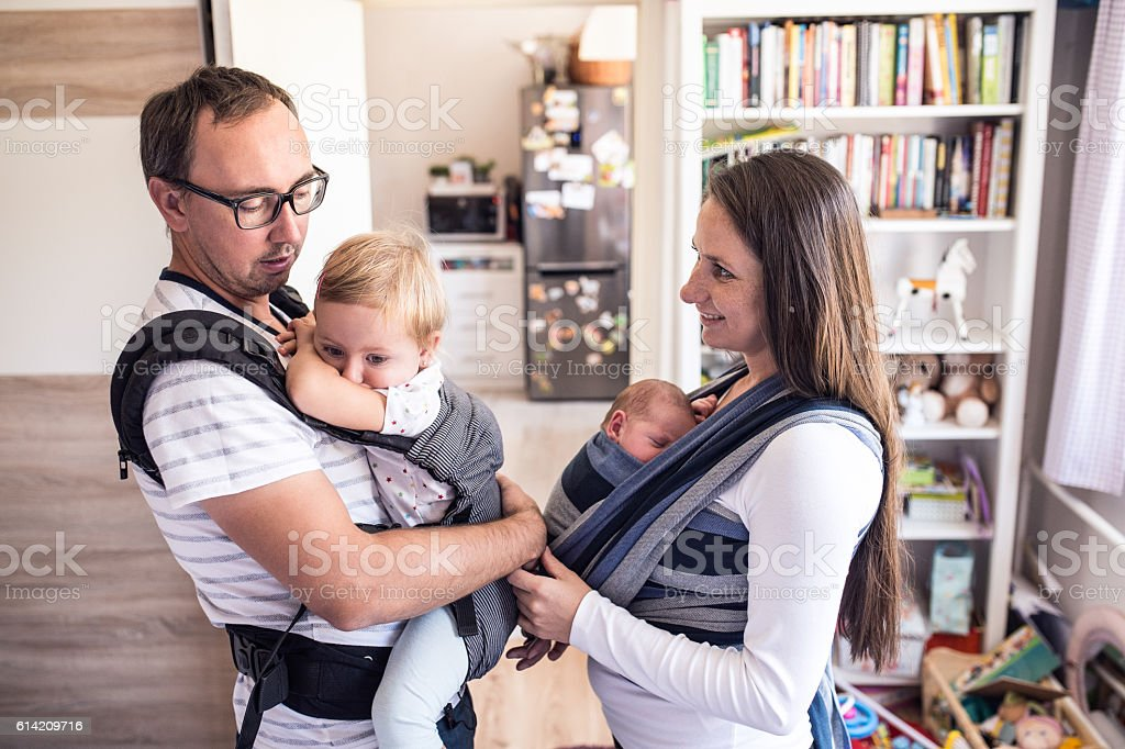 Young parents with children in sling and baby carrier stock photo