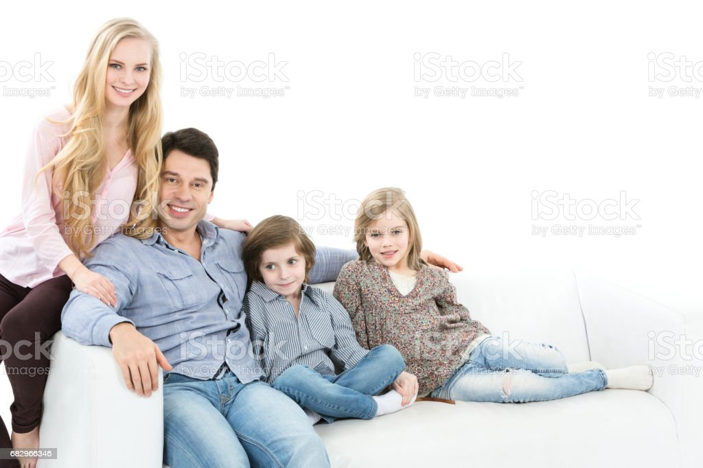 Young parents with children on the couch isolated. royalty-free stock photo