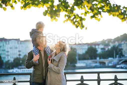 Young parents with their toddler son standing outdoors by the river in city of Prague at sunset.