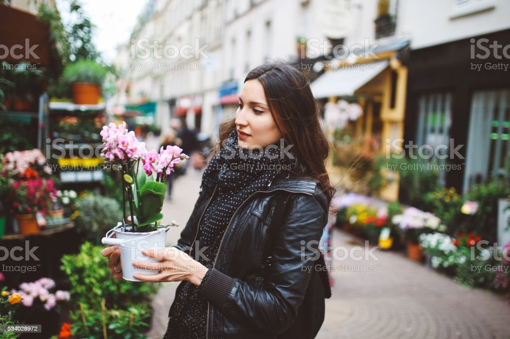 Young Parisian woman buying flowers on the streetmarket stock photo