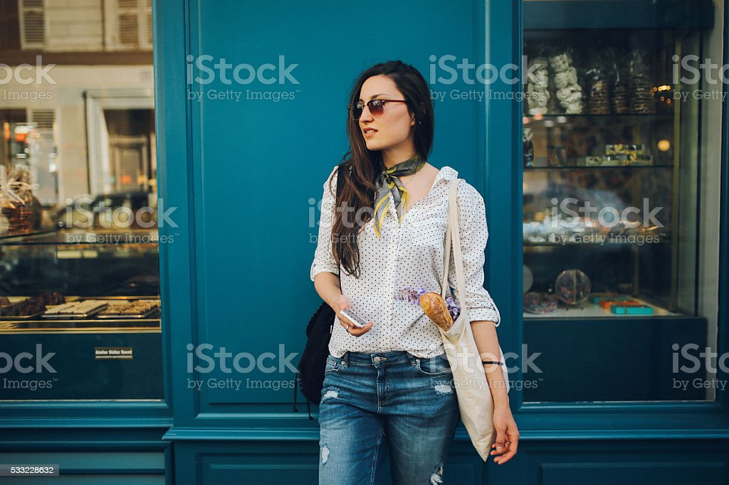 Joven mujer comprando parisino en una panadería - foto de stock