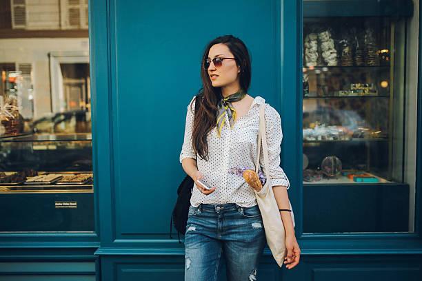 joven mujer comprando parisino en una panadería - moda parisina fotografías e imágenes de stock