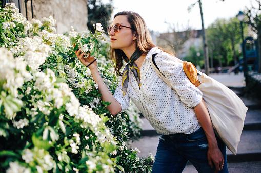 Young Parisian woman enjoying flowers
