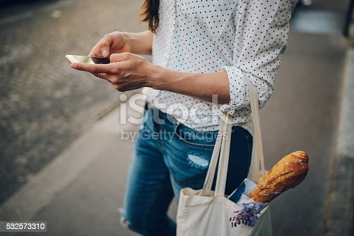 Vintage toned image of a young Parisian woman using her smartphone while walking the streets on Montmartre district of Paris. She is wearing a white dotted pattern shirt and sunglasses, carrying a canvas tote bag after some shopping for groceries and food. Paris, lifestyle, street style fashion concepts.