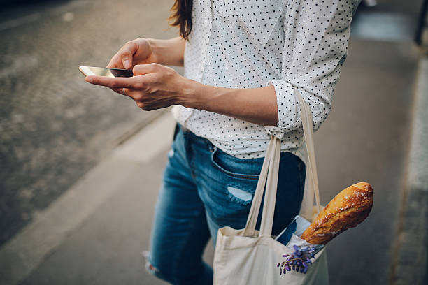 young parisian woman using the smartphone - preppy fashion stock photos and pictures