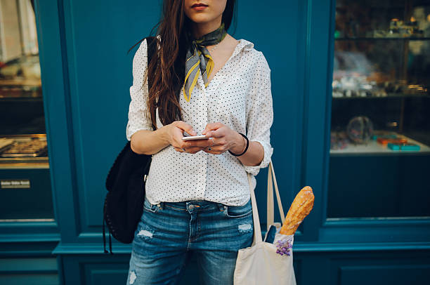 young parisian woman using the smartphone - paris fashion stock photos and pictures