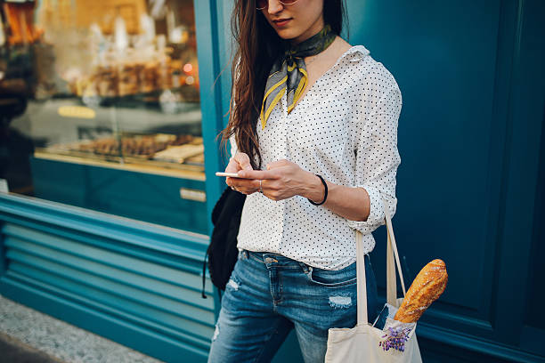 Young Parisian woman using the smartphone stock photo