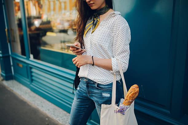 junge pariser frau benutzt dem smartphone - genießen französisch stock-fotos und bilder