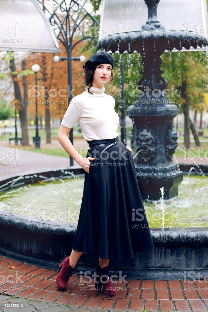 Young Parisian woman wearing black beret walking under the rain. Melancholic autumn mood. stock photo