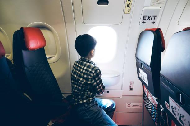 Junger Passagier, der allein an Bord eines Verkehrsflugzeugs reist – Foto