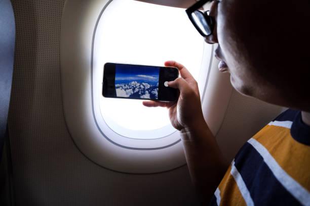 Junger Passagier mit Smartphone an Bord eines Verkehrsflugzeugs – Foto