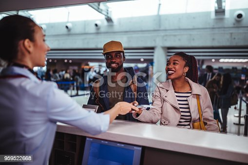 Young African-American couple doing check-in at airline check-in counter at international airport