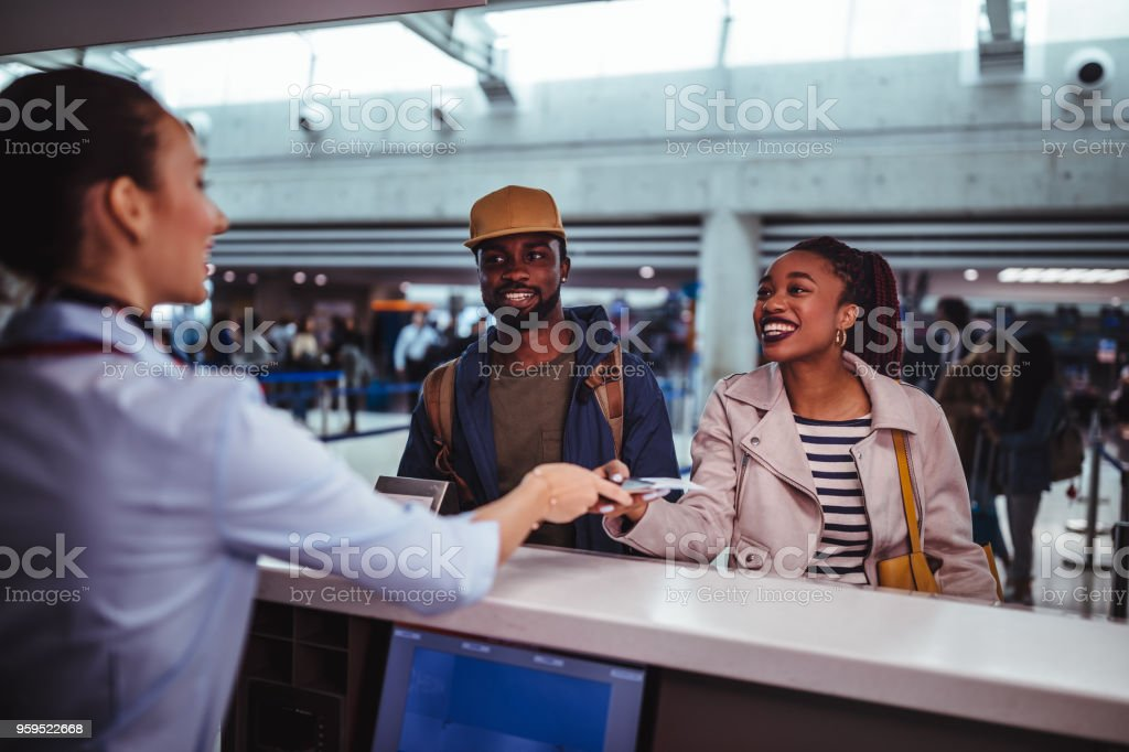 Young passengers doing check-in for flight at airport stock photo
